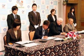 協定書に調印する萩原市長(前列左から2人目)とボベット理事長(同3人目)