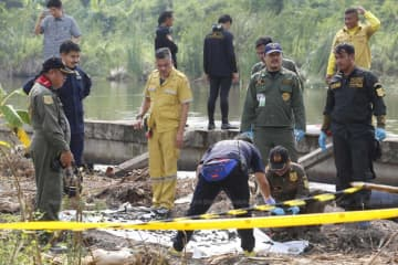 Almost 300 human bone fragments were retrieved from a large pond near the home of a 40-year-old man in Bang Khae district of Bangkok on Friday. He was charged last week with murdering a woman and concealing her body. (Photo by Pornprom Satrabhaya)