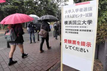 冷たい雨が降る中、会場に向かう受験生=18日、横浜市保土ケ谷区の横浜国立大学