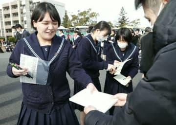 試験を終え、問題用紙を教員に渡す受験生=18日、大分市の大分大旦野原キャンパス