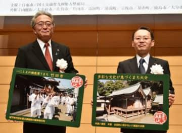 歴史まちづくりカードを手にする首藤勝次竹田市長(左)と桑田龍太郎大分市副市長=宮崎県日南市