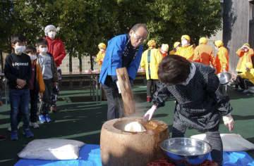 【きねで餅つきをする北川会長(中央)=亀山市関町新所の道の駅「関宿」で】