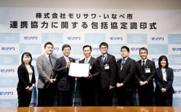 【協定書を手にする日沖市長(左から4人目)、森澤社長(同3人目)ら=いなべ市役所で】