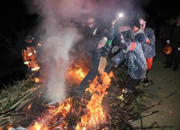 炎の中に投げ込まれる若者=14日夜、伊勢原市神戸地区