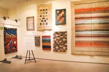 イランのじゅうたん「ギャッベ」(左)など、遊牧民の暮らしをデザインした作品も並ぶ=県立地球市民かながわプラザ提供