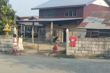 Children walk past a house in Ban Tha Luang in Phimai district of Nakhon Ratchasima on Sunday, where villagers hang red shirts on their fences in the belief that the practice will ward off a murderous ghost. (Photo by Prasit Tangprasert)