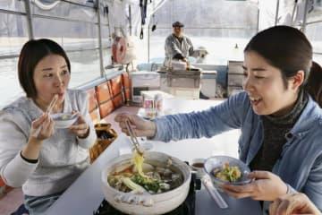 台風19号による豪雨被害を受けた「阿武隈ライン舟下り」で、復活した「しし鍋」を堪能する観光客=19日、宮城県丸森町
