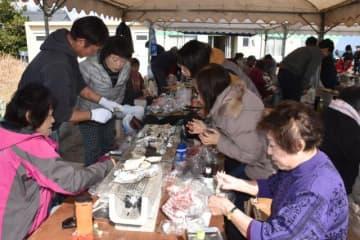 殻の開け方などを学び、カキを食べる参加者