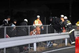 事故現場を調べる警察官と消防隊員=三田市三輪2
