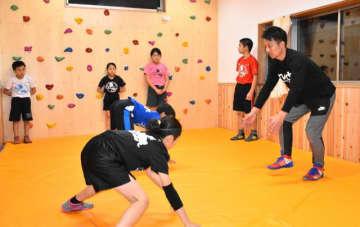 自費で建てたレスリング練習場で子どもたちを指導する鈴木博也さん(右)=串間市