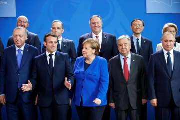 19日、ベルリンで開かれたリビア和平国際会議に出席したドイツのメルケル首相(前列中央)ら各国首脳(ロイター=共同)