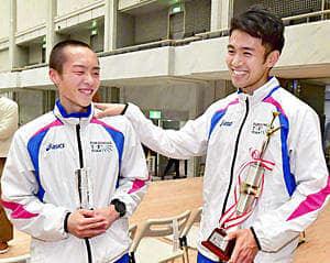 優秀選手賞や区間賞のトロフィーを手に、健闘をたたえ合う相沢(右)と松山=19日午後、広島市