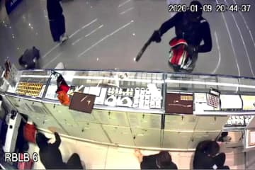 Police investigators are questioning a man in relation to the Aurora gold shop heist in Lop Buri. (Screen capture from a security camera of the Aurora gold shop)
