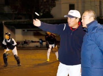 真剣なまなざしで野球部の練習をみつめる王熙杰さん(右)=17日、川之江高校