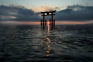 午前7時すぎ、白鬚神社の大鳥居の奥から昇る朝日が湖面にきらめく(2019年12月25日、滋賀県高島市鵜川)