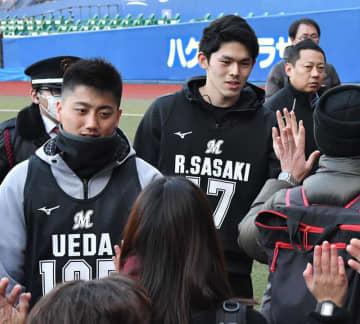 練習後にファンとタッチする佐々木朗(中央)と植田(左)