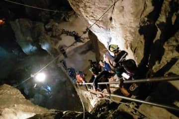 Rescuers descend a staircase to the ground floor of Tham Takfa cave in Nakhon Si Thammarat's Phrom Khiri district, where a monk was found dead after a fall on Saturday. (Photo by Nujaree Raekrun)