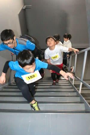 ビルの階段を駆け上がる「ビルクライムカップ」の参加者ら=19日、新潟市中央区