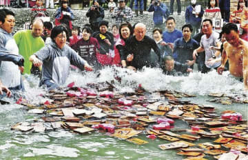 水しぶきを上げながら札に駆け寄る参加者(19日、和歌山県田辺市本宮町で)