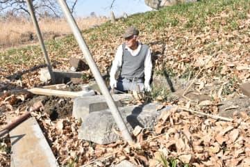 谷中村史跡の共同墓地で修繕作業をする水野さん=14日午前、栃木市藤岡町の渡良瀬遊水地