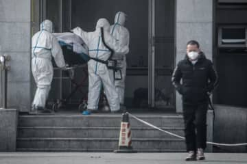 Medical staff members carry a patient into the Jinyintan hospital, where patients infected by a mysterious SARS-like virus are being treated, in Wuhan in China's central Hubei province on Saturday. (AFP photo)