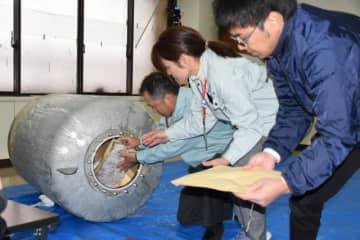 タイムカプセルから収容物を取り出す都城市高崎総合支所の職員