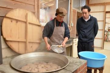 岡田原史さん(左)が手作りしたこんにゃくの唐揚げの販売に取り組む重信誠さん