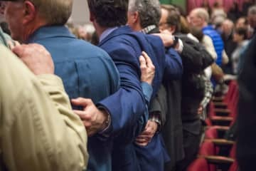 Supporters of a Jewish solidarity event embrace as they sing a song Jan. 6 at Byers Theatre in Sandy Springs. This event was held in response to the recent hate attacks in New York and New Jersey. - ALYSSA POINTER/Atlanta Journal-Constitution/TNS