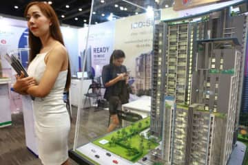 Salespersons wait for potential customers at a residential fair in Bangkok. The government has eased mortgage conditions to boost liquidity pending the passage of the 2020 budget bill. (Bangkok Post file photo)