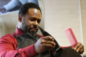 Principal Terrance Newton focuses while using the clippers as he gives student Michael Harley, 8, a haircut at Warner Elementary School in Wilmington, Del. on Jan. 14, 2020. - David Maialetti/The Philadelphia Inquirer/TNS