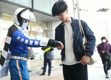 通行人に交通安全を呼び掛ける県警オリジナルキャラクターのゼブラストップマン(左)=20日、大分市中央町