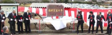 駅館川東岸の台地に水を引く広瀬井路の通水150年記念碑の除幕をする関係者ら=宇佐市金屋の金屋公園