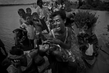 A Rohingya refugee reacts while holding his dead son after crossing the Naf river from Myanmar into Bangladesh on October 9, 2017, about two months after operations by the Myanmar military began.