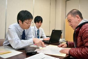 店舗が被災し、職員(左)から補助金申請にの説明を受ける事業者=20日、久慈市役所