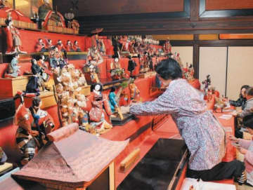 6段のひな壇に江戸時代中期から明治期の人形を展示。6人がかりで木箱から出して組み立てた人形を丁寧に配置していった=20日、日田市豆田町