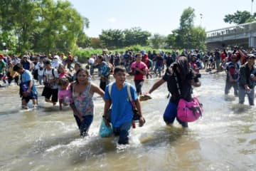 Central American migrants — mostly Hondurans travelling in a caravan to the US — cross the Suichate River between Guatemala and Mexico, where Mexican forces fired tear gas trying to force them back.