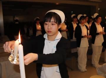 ろうそくに火をともす実習生=佐世保市、九州文化学園歯科衛生士学院