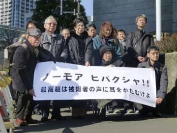 原爆症認定を巡る訴訟の上告審弁論で最高裁に向かう原告と弁護士、支援者ら=21日午後、東京都千代田区