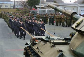 先輩隊員の力を借りて、重さ約38トンの戦車を動かす新成人の自衛官ら=高島市今津町・陸上自衛隊今津駐屯地
