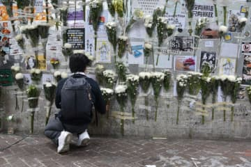 A person lays white funeral flowers outside an exit of Prince Edward MTR station on October 31. Photo: Jimmy Lam/United Social Press.