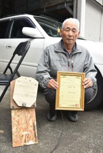 独自に開発したペダル装置(左)と、特許証を持つ小笠原和夫さん