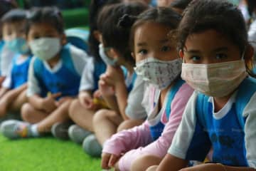 Students at Songwitthaya School in Muang district of Samut Prakan province wear face masks as the levels of unhealthy smog exceed safety standards in many areas in Bangkok and surrounding provinces on Tuesday. (Photo by Somchai Poomlard)