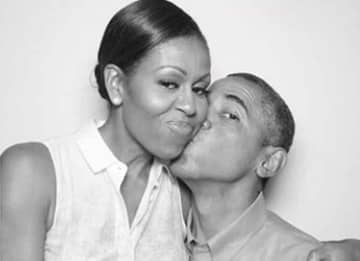 Michelle Obama kissed by husband Barack Obama