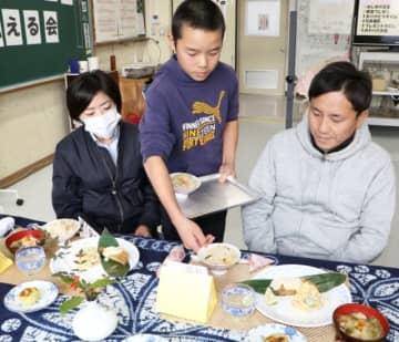 自分たちで作った「ありがとう御膳」を保護者に配膳する新田小6年の男子児童=豊後大野市三重町