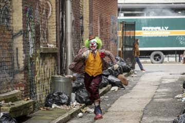 "Joaquin Phoenix's Arthur Fleck gets jumped by some teenagers early in the film ""Joker."" The production filmed on Newark's Market Street near the marquee for the old Paramount Theatre. Storefronts were transformed into pornography theaters."