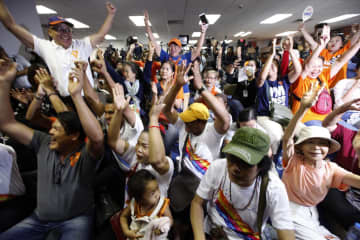 Supporters of the Future Forward Party celebrate after the Constitutional Court acquitted the party of attempting to overthrow the constitutional monarchy — a charge which could have lead to its disbandment if found guilty.Wichan Charoenkiatpakul