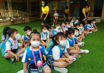 Students in Samut Prakan's Muang district wear face masks as they arrive at Songwitthaya School, where teachers briefed them on how to protect themselves from hazardous PM2.5 dust particles. Photo by Somchai Poomlard