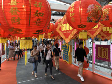 Pedestrians on the skywalk connecting Asok skytrain station with Terminal 21 shopping mall, which has been decorated for Chinese New Year. Sarot Meksophawannakul