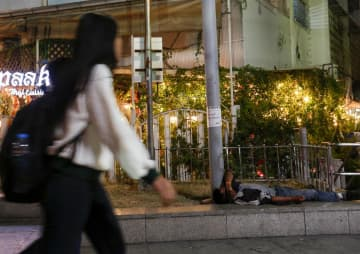 A woman walks past a homeless man in Bangkok. Thailand's inequality is among the highest in the world. PATTARAPONG CHATPATTARASILL