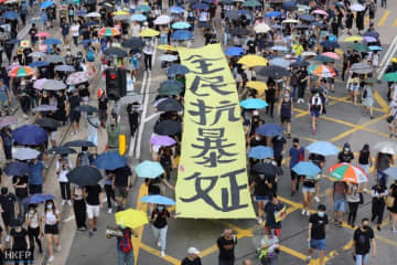 "Protesters held a large banner reading: ""The people rise up against the tyrannical regime."" Photo: May James/HKFP."